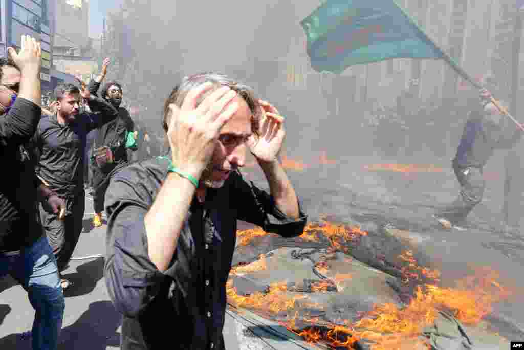 Iranian and Iraqi Shiite Muslims run past a burning tent during the reenactment of the events of the 10th day of the month of Muharram, which marks the peak of Ashura, in the Iranian capital of Tehran on August 30.