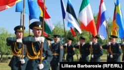 Militari moldoveni purtând drapelele ţărilor membre ale NATO