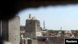 A destroyed minaret at the Grand Al-Nuri Mosque is pictured through a hole at an Iraqi-held position in the Old City in Mosul on June 27.