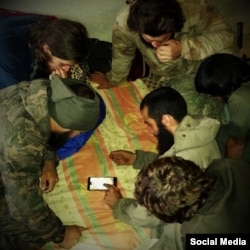 An image taken from an Islamic State (IS) social media account purportedly showing militants from IS Katibat Al-Aqsa using Google maps on a cellphone to help plan the Kobani offensive.
