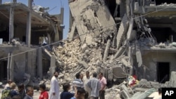 Members of the media and others examine the remains of a damaged residential building in Tripoli on June 19, 2011