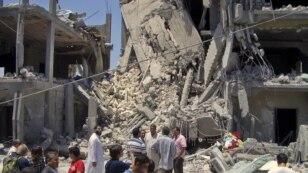 Predstavnici medija hodaju po ostacima oštećenih stambenih zgrada u Tripoliju, 19. jun 2011.