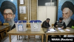 Poll workers are seen during parliamentary elections at a polling station in Tehran, February 21, 2020