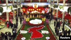 North Korea -- People look at flowers during the 16th Kimjongilia Festival to mark the birth anniversary of the late leader Kim Jong-Il in Pyongyang, 14Feb2012