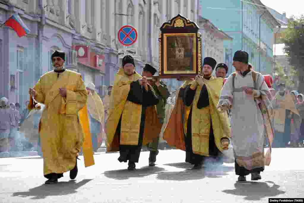 Orthodox clergymen carry the venerated icon of St. Nicholas.