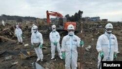 Префектура Фукусима: полицейские в защитных костюмах во время минуты молчания в память о погибших 11 марта