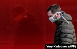 """A man wearing a face mask walks along a street in Moscow on March 23. """"The number of people who are sick is significantly higher in reality,"""" said Moscow Mayor Sergei Sobyanin."""