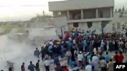 سوريون يتجمعون حول مبنى تعرض لإنفجار في مدينة حماة السورية