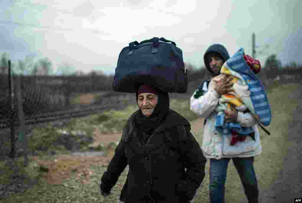 A woman balances a bag on her head and a man carries a child as migrants and refugees make their way across the Macedonia-Serbia border at Tabanovce. (AFP/Robert Atanasovski)