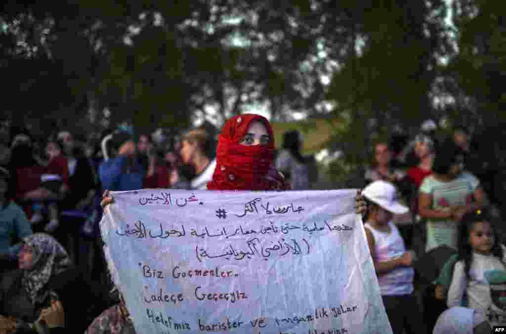 """Сирийская женщина на сухопутной границе Турции и Греции держит в руках плакат с надписью: """"Мы беженцы! Мы все равно пройдем в Европу"""". 17 сентября"""