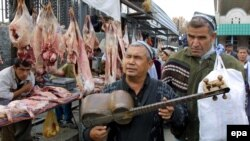 A blind Uzbek musician sings traditional songs while playing a tar at a bazaar in Tashkent.