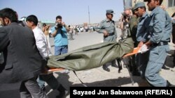 Afghan officials carry the body of a militant who died in the attack on the police station