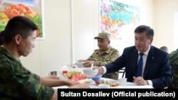 Президент Сооронбай Жээнбеков кыргыз армиясынын жоокери менен тамактанууда. 2018-жыл.