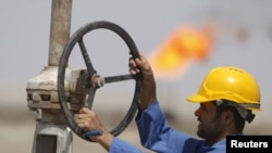 A worker adjusts a pipe at the Nassiriyah oil field, southeast of Baghdad.