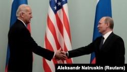 Премьер-министр России Владимир Путин пожимает руку вице-президенту США Джо Байдену во время их встречи в Москве, 10 марта 2011 года.