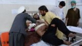 Relatives move a victim onto a bed as he receives treatment at a hospital following multiple explosions that targeted a cricket stadium in Jalalabad on May 19. Eight people were killed.