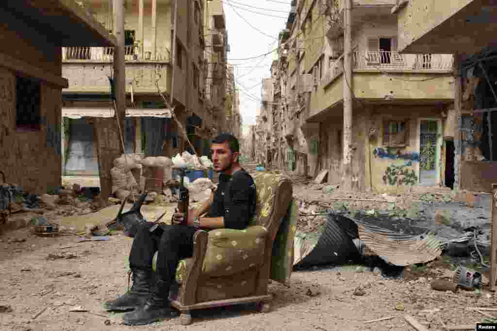 A member of the Free Syrian Army holds his weapon as he sits on a sofa in the middle of a street in Deir al-Zor. (Reuters/Khalil Ashawi)