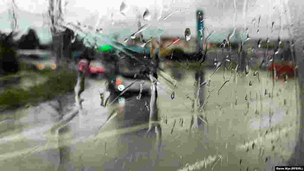 Вода стекает по стеклам автомобиля
