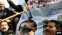 """محتجون مصريون يستخدمون """"حذاءً وفرشاة تنظيف"""" في ضرب صورة لحسني مبارك"""