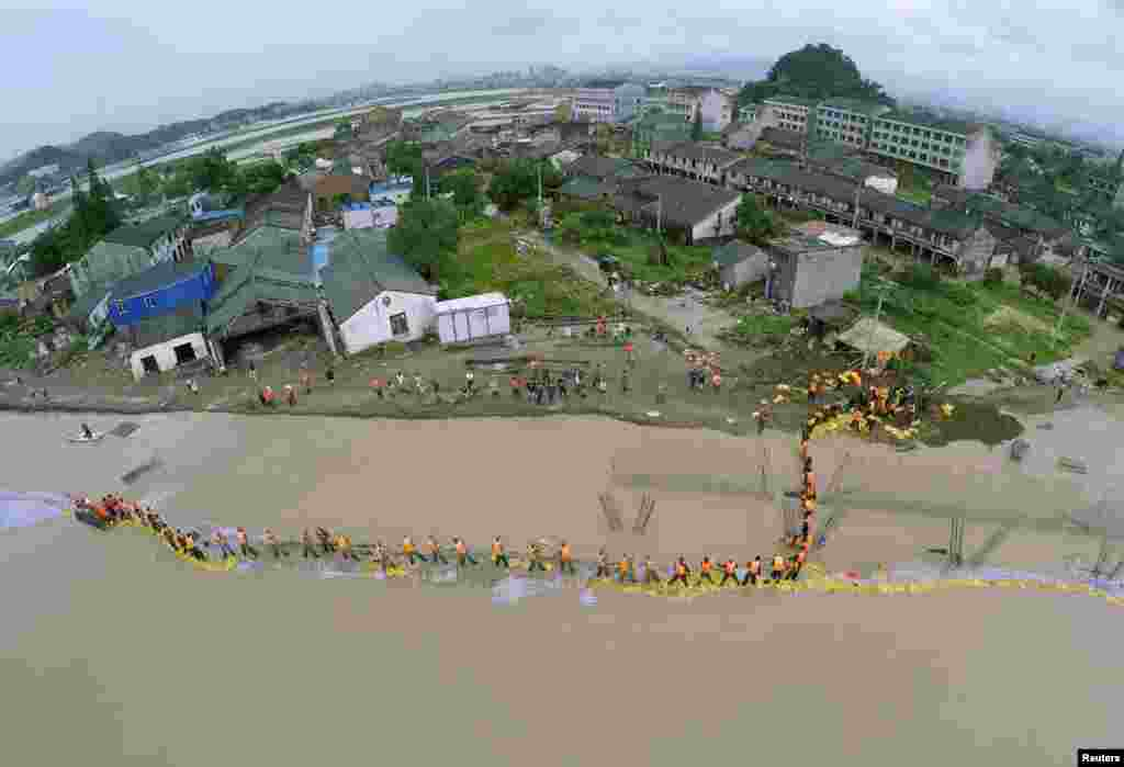 An aerial view shows People's Liberation Army soldiers and local residents placing sandbags to block floodwaters after a dam breached under the influence of Typhoon Soudelor in China's Zhejiang Province. Typhoon Soudelor battered China's east coast on August 9, killing 14 people and forcing the authorities to evacuate hundreds of thousands more. (Reuters/China Daily)