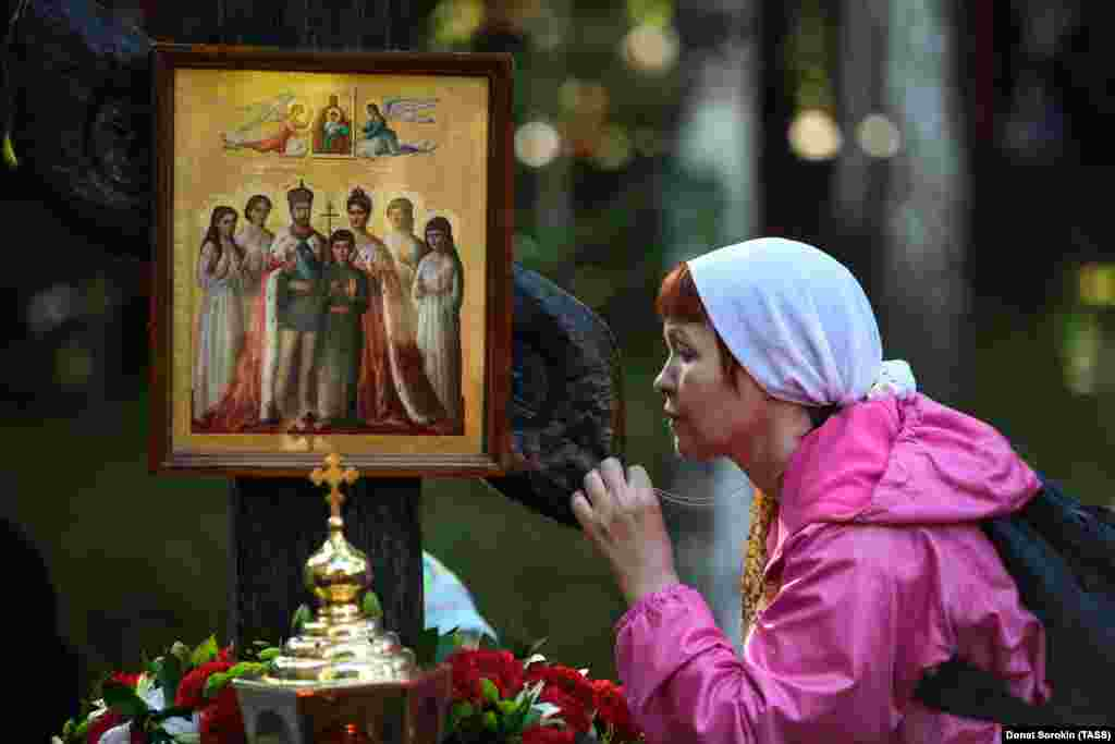 A woman kisses a cross with a portrait of the tsar, tsarina, and their five children. In 2000, the Russian Orthodox Church canonized the Romanov family.