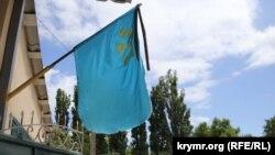 Крымскотатарский национальный флаг с траурной лентой. Иллюстрационное фото