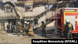 Сотрудники департамента по чрезвычайным ситуациям рядом со сгоревшим зданием в Масанчи.