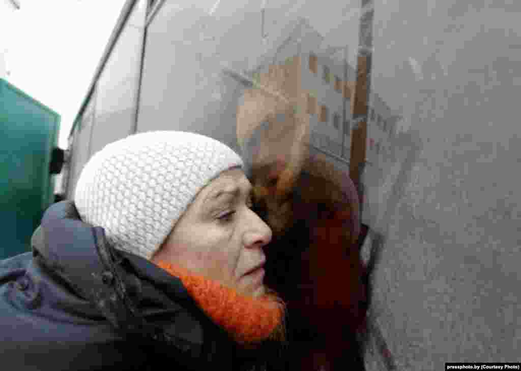 A woman tries to hear what her relative in a police bus is saying following an antigovernment protest in Minsk. Photo by Vasil Fyadosenka