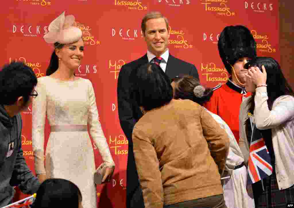 People inspect wax figures of Britain's Catherine, Duchess of Cambridge (left), and Prince William at a press preview in Tokyo. The Madame Tussauds museum in Tokyo will be reopened in March 2013 with more than 60 waxworks expected to be displayed. (AFP/Yoshikazu Tsuno)