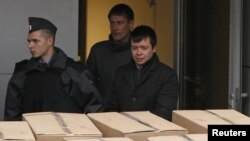 Detained opposition activist Konstantin Lebedev (right front) is escorted out of a building of the Russian Investigative Committee in Moscow on October 17.