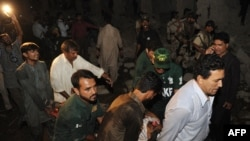 Rescuers and security personnel remove an injured victim at the site of the Karachi bombing.
