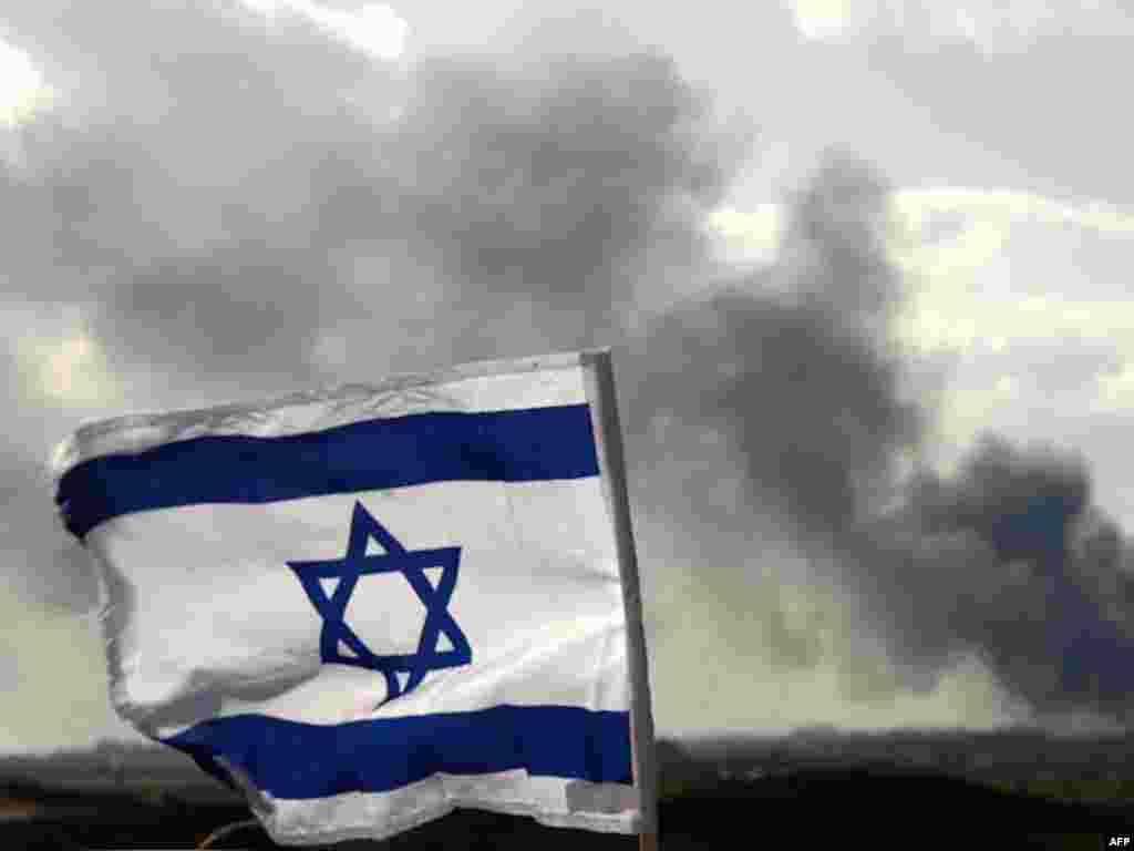 Israel -- The Israeli flag flutters on a hill near the border with the Gaza Strip as smoke from Israeli strikes covers Gaza, 09Jan2009 - ISRAEL, Israeli-Gaza Border : The Israeli flag flutters on a hill near the border with the Gaza Strip as smoke from Israeli strikes covers Gaza on January 9, 2009 top2009