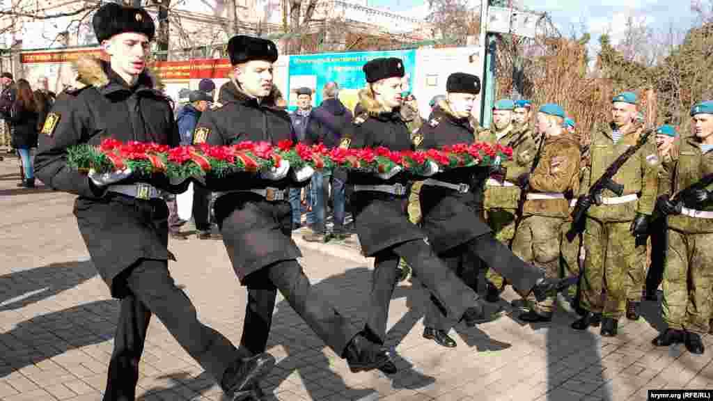 Російські військовослужбовці у флотській корабельній формі проводять тренування щодо покладання гірлянди квітів до меморіалу загиблим в Афганістані