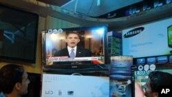 دو مرد افغان سخنرانی باراک اوباما را از تلویزیون دنبال میکنند- افغانستان، اول تیرماه