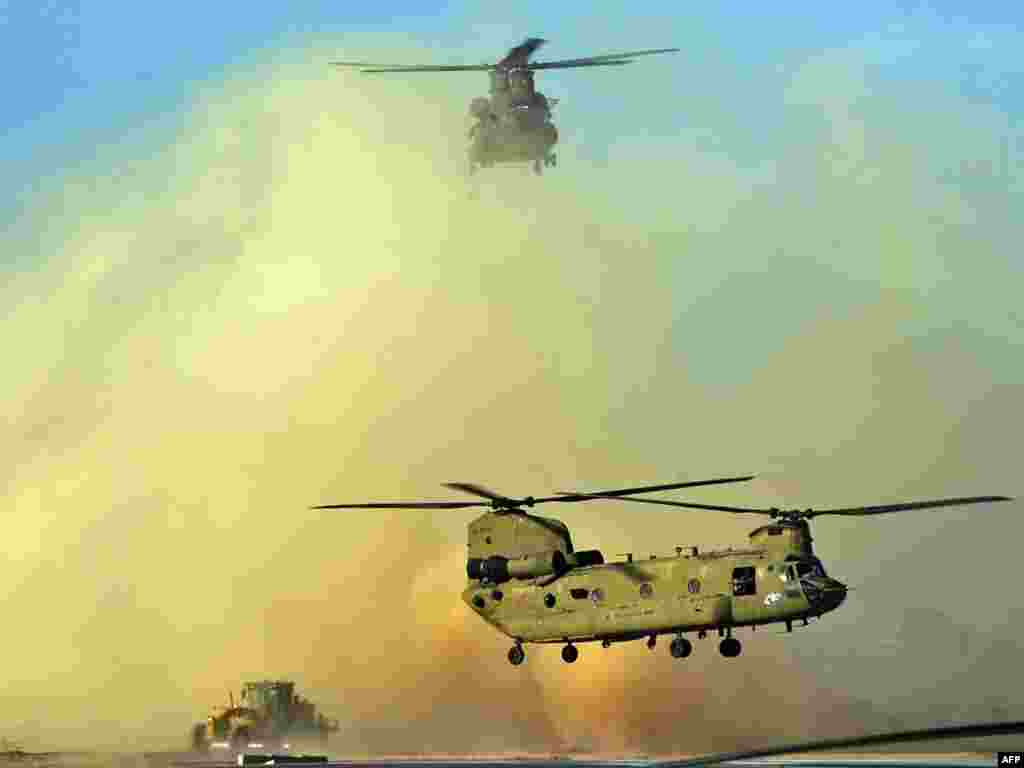 Two U.S. Army Chinook helicopters land at Kandahar airfield in southern Afghanistan on March 30. Photo by Peter Parks for AFP