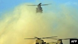 Two U.S. Chinook helicopters land at Kandahar airfield in March 2011.