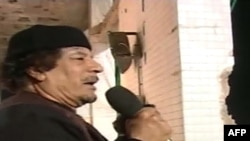 Muammar Qaddafi speaks at his former Bab al-Aziziya residence in Tripoli on March 23.