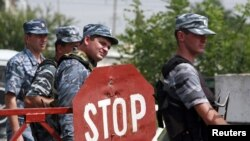Police officers stand at a checkpoint near the border with Ingushetia, where a suicide bomber blew himself up near the village of Chermen, on August 17.