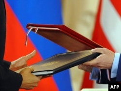 U.S. President Barack Obama and his Russian counterpart, Dmitry Medvedev, exchange the signed New START Treaty in Prague in April 2010.