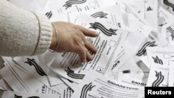 Ukraine -- A member of a local election commission takes a ballot after all ballots were taken from a ballot box as the commission start counting votes of today's referendum on the status of Luhansk, May 11, 2014