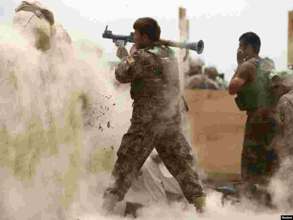An Afghan Army soldier fires a rocket-propelled grenade at suspected Taliban militants at Combat Outpost Nolen in the Arghandab Valley north of Kandahar on July 22. Photo by Bob Strong for Reuters