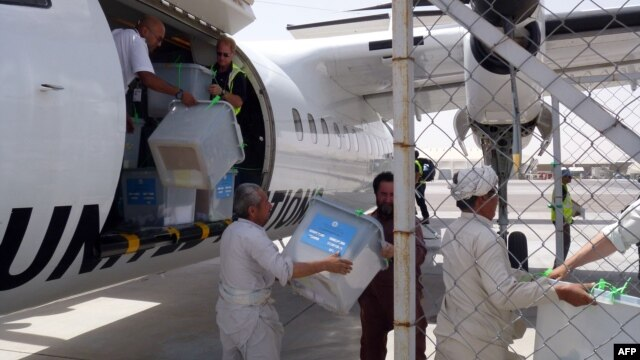 Afghan election commission workers, overseen by NATO-led Italian troops, unload ballot boxes flown in on a UN aircraft from Farah Province and to be sent onward to Kabul, at Herat airport on July 24.