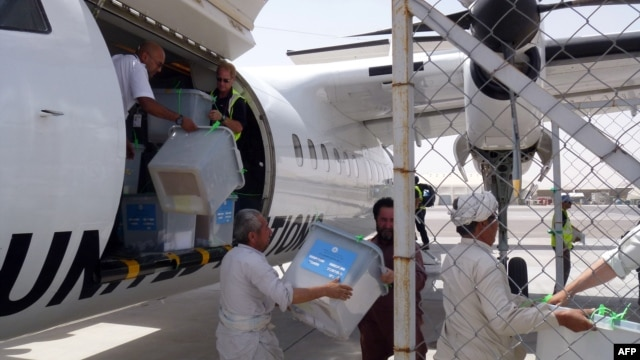 Independent Election Commission workers, overseen by Italian troops, unload ballot boxes flown in on a UN aircraft from Farah Province to be sent onward to Kabul, at Herat airport on July 24.
