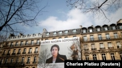 FRANCE -- A banner with a giant portrait of jailed Iranian lawyer Nasrin Sotoudeh by Arash Ashourinia is seen on the headquarters of the French National Bar Council, demanding her release, in Paris, March 28, 2019