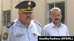 "Editor Hilal Mamedov (right) of the Talysh-language independent newspaper ""Tolishi Sada"" is escorted by police in Baku on June 22."