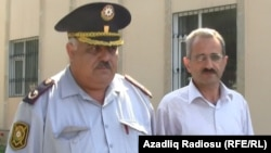 """Editor Hilal Mamedov (right) of the Talysh-language independent newspaper """"Tolishi Sada"""" is escorted by police in Baku on June 22."""
