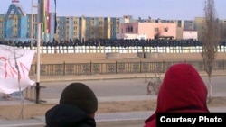 Locals watch in January as security forces occupy the square in Zhanaozen where clashes killed at least 16 people on December 16.