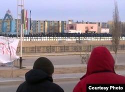 Двое мужчин смотрят на выстроенных вооруженных полицейских. Жанаозен, январь 2012 года.