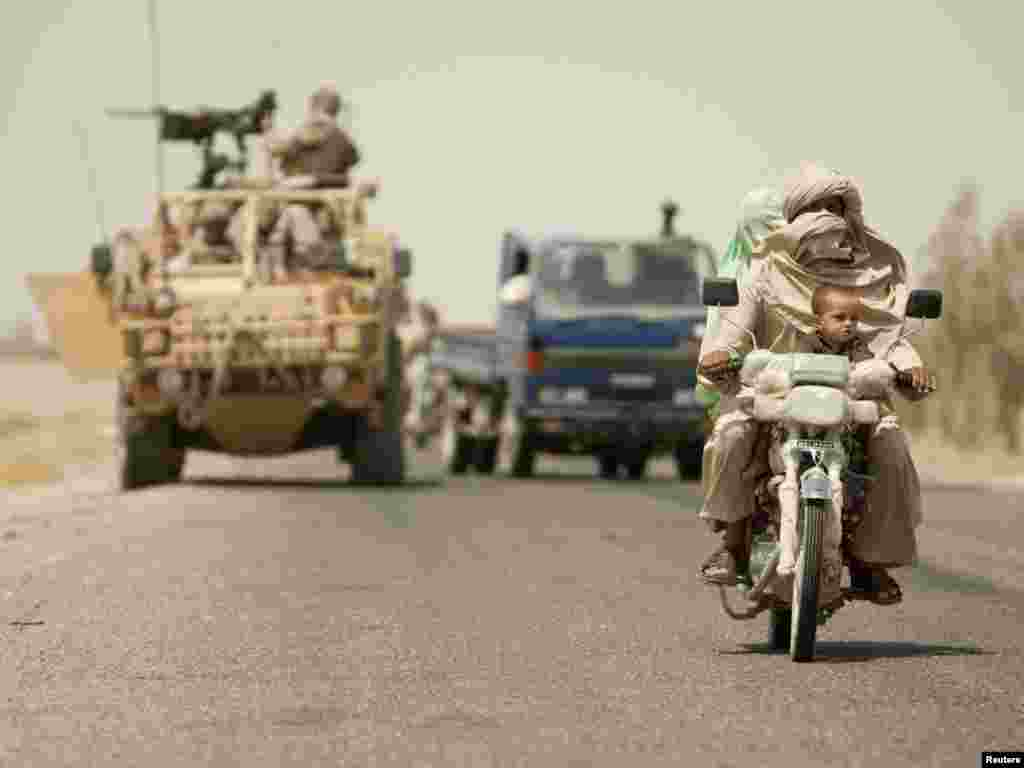 An Afghan family rides on a motorcycle in front of a British armored vehicle at a joint checkpoint with Afghan National Police outside the town of Lashkar Gah in Helmand Province.Photo by Shamil Zhumatov for Reuters