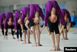 На занятиях по гимнастике в школе в китайском городе Шенян. 9 мая 2012 года.